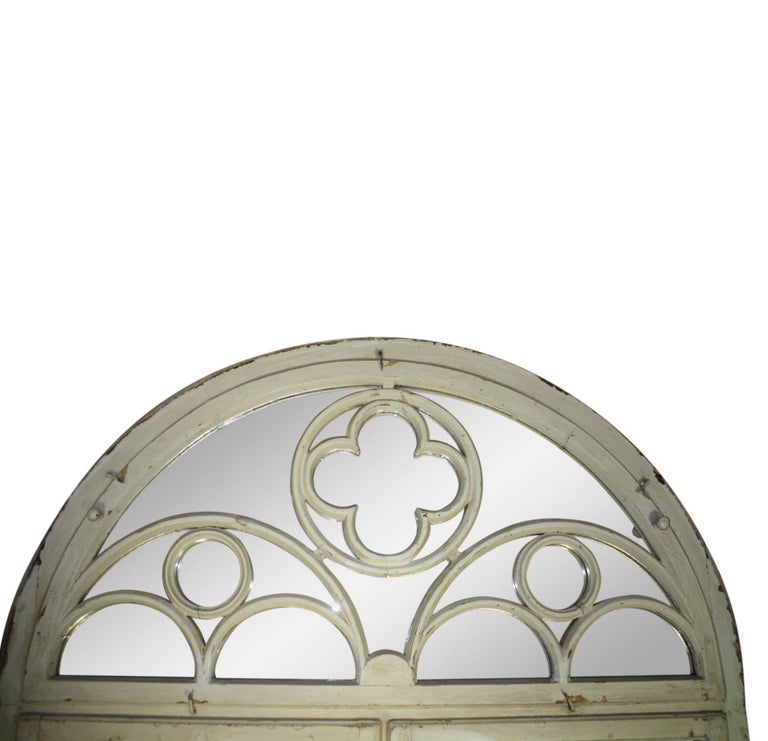 Originally a large, casement window from the turn of the century, the glass panes of the window were later removed and replaced with pieces of mirror. The mirror is comprised of two hinged frames with eight panes on each. An arch above features a