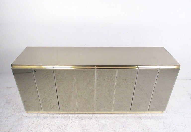 This stylish mirrored finish credenza with bronze finish trim, open cabinet adjustable shelf storage, and an interior drawer. Perfect sideboard buffet for dining room service, showroom storage, or office use. Impressive Ello style cabinet makes a