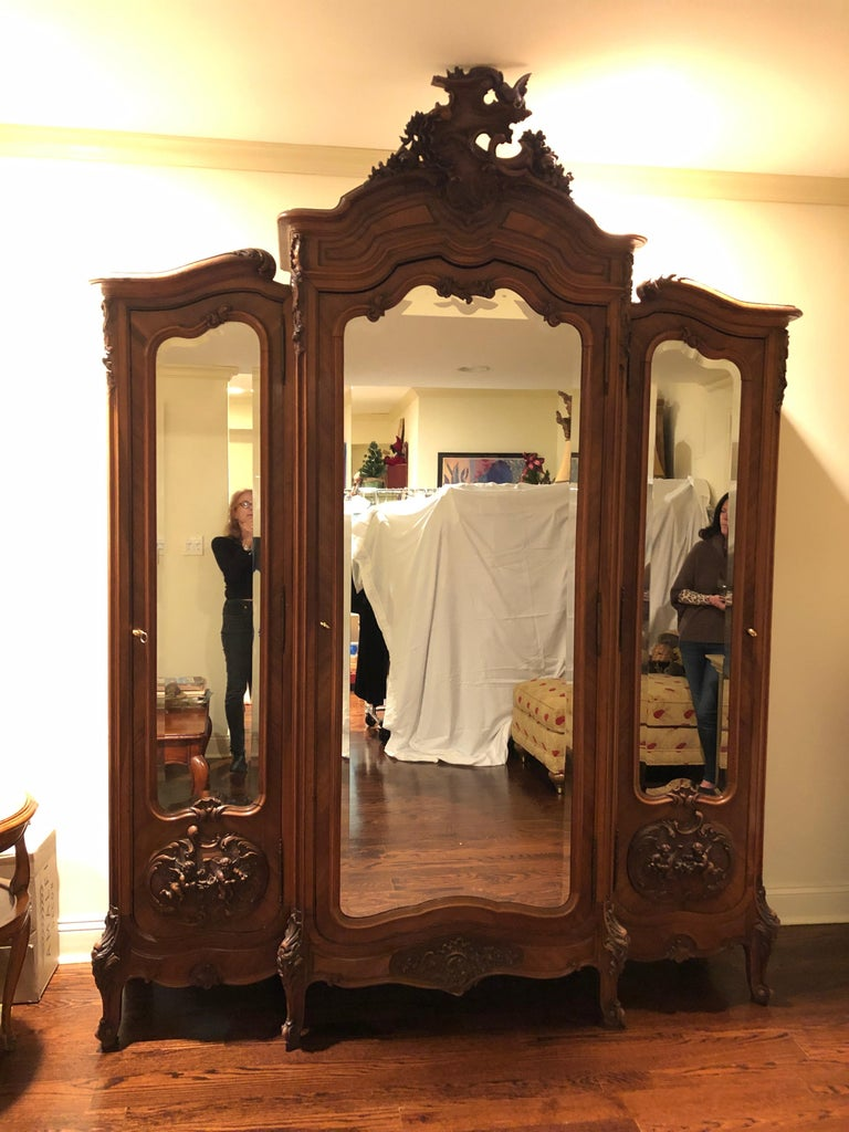 Louis XV style 3-part relief carved walnut and walnut veneer parquetry inlaid, beveled mirror armoire, second half of the 20th century, having incredible carved crest able a serpentine moulded cornice, central mirrored door flanked by conforming
