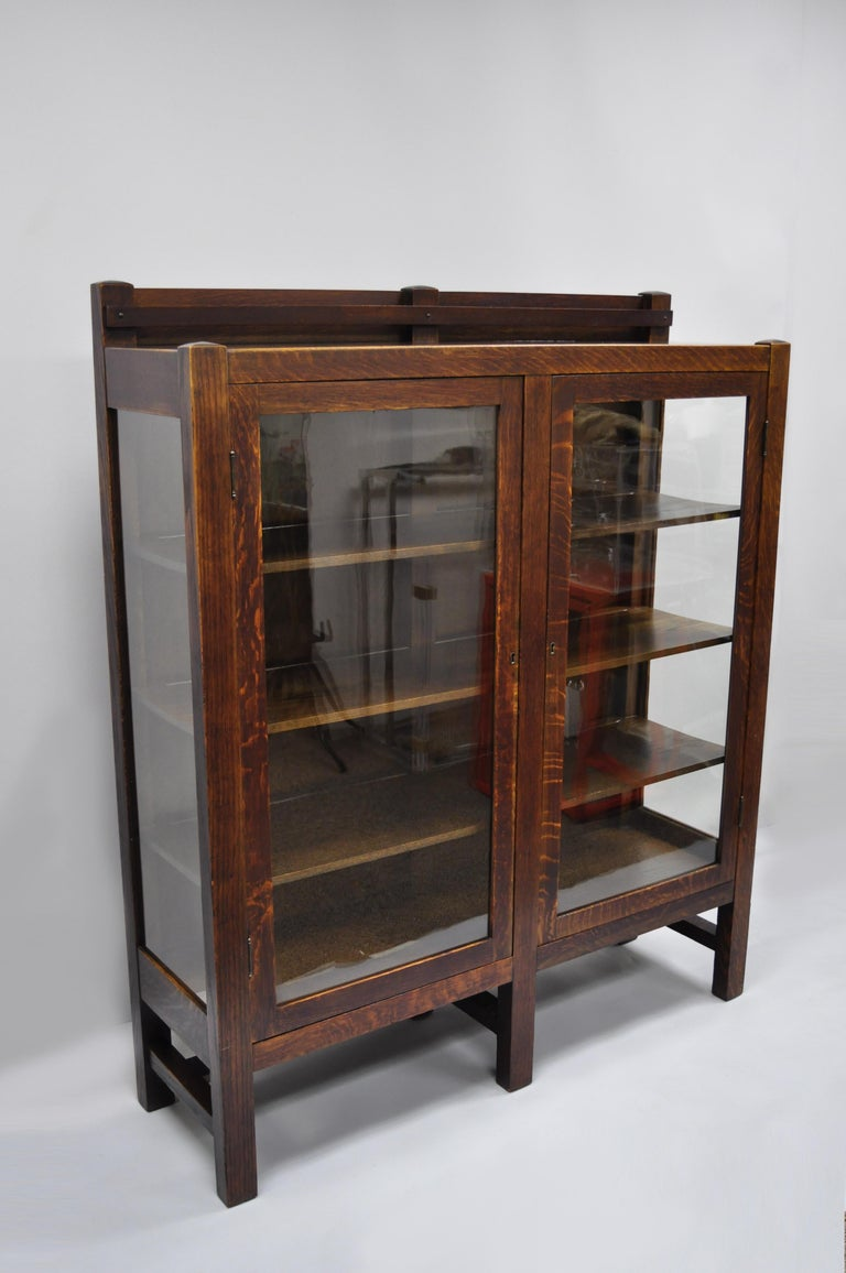 Mission Arts & Crafts Stickley era glass double door China cabinet bookcase. Item features 6 legs, stretcher base, 2 glass doors, glass sides, solid wood construction, beautiful wood grain, working lock and key, 3 wooden shelves, quality American