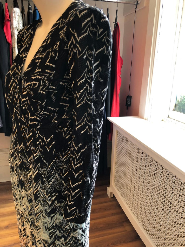 This dress has an unusual abstract zig zag pattern with an ombre graded look.  Black and white at the top with aqua, orange, black and white at the bottom. The neckline is v-shaped and closure is by a zipper on the side. Easy to wear day or evening!