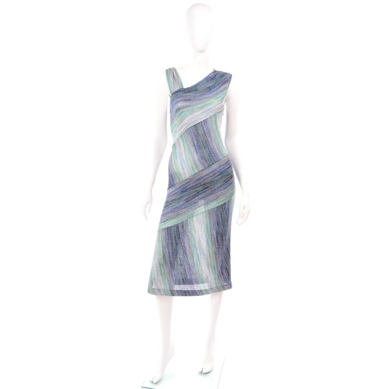 This is a very pretty Missoni metallic purple, green and blue knit dress with alternating vertical and horizontal abstract striped pattern. This dress slips overhead and has asymmetrical shoulder styling.   Labeled an Italian size 44 and we estimate