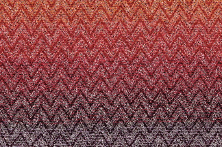 Throw in shaded wool blend with lurex applications and iconic Missoni geometric chevron print. Throw in warm shades of red, purple and blue with neutral tone fringe trim. Presented in a branded gift box. Perfect for adding an elegant touch to any