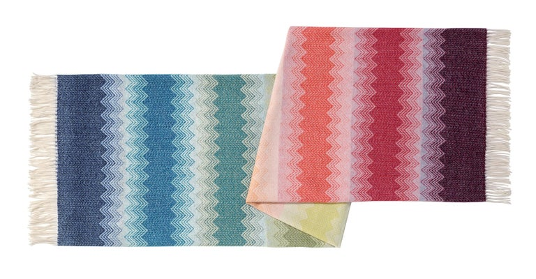 MissoniHome's iconic chevron pattern in a wool jacquard throw with a rainbow color-blocked-effect and fringed edges; size 55 x 75 inches. Presented in a branded MissoniHome box.