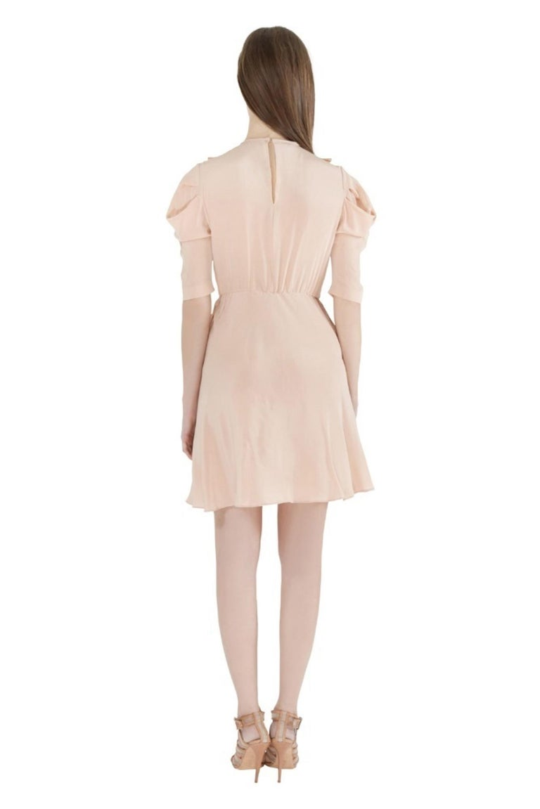 Super feminine and pretty, this Miu Miu dress will definitely fetch you lots of compliments. The lovely ruffle trims, lace inserts at the front and subtly pleated sleeves make this dress a woman's dream. Team it with strappy sandals for your dinner