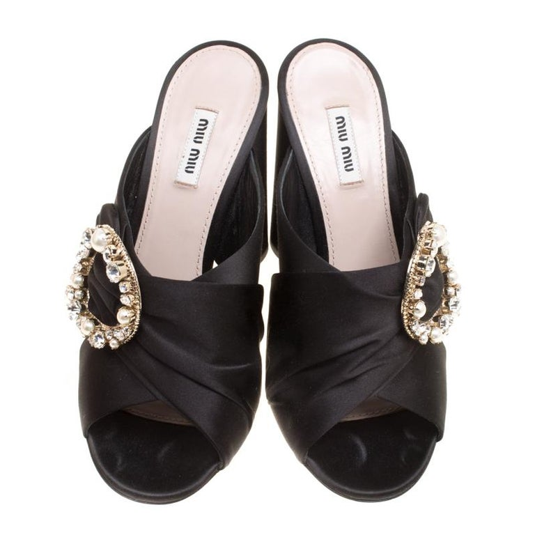 Ravishing, resplendent and regal, these mules from Miu Miu will take your breath away! The black mules are crafted from satin and feature a peep-toe silhouette. They flaunt crossover vamp straps with an exquisite crystal and faux pearl embellished