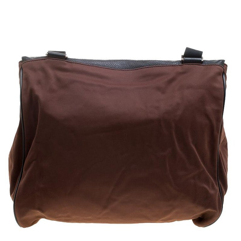 Guys can now move round in style by carrying this classy messenger bag made from a combination of nylon and leather. It has a fleshy structure that provides the spacious interiors and also has a small front pocket. It can be closed with the slip