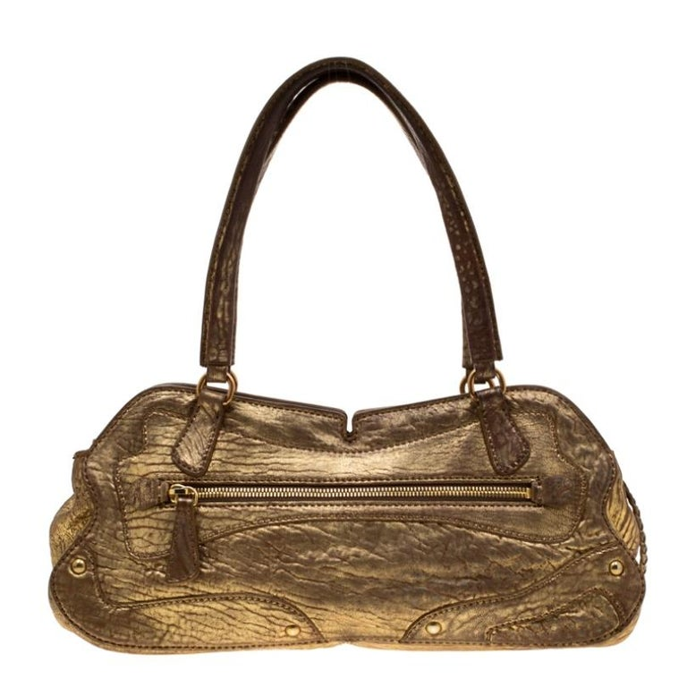 Travel light with this distressed leather bag created in metallic gold shade. Secured by a zipper, this opens to a fine fabric lined interior that is sure to house your essentials safely. This Miu Miu shoulder bag features two top handles and a