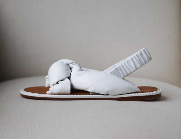 Miu Miu's footwear is known for its playful and unexpected proportions, these current season sandals have been made in Italy from pristine white leather that's padded and artfully knotted. Slight heel White leather (Lamb) Elasticated slingback