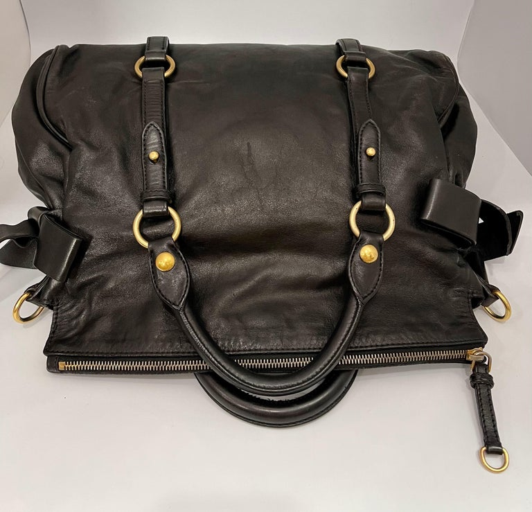 Polished calfskin leather in black with large leather bows on the sides. Rolled leather top handles, an optional shoulder strap, belt embellishment around the girth, and polished brass hardware including large hoop links. The fold-over zip top opens