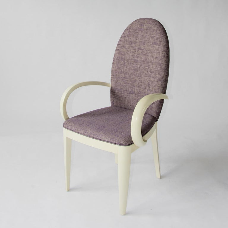 Characterized by a soft, curved design, the M&M chair with armrests has a structure made from wood with an ivory lacquered finish. The comfortable chair has been upholstered in a purple melange fabric and combined with the light tone of the wood