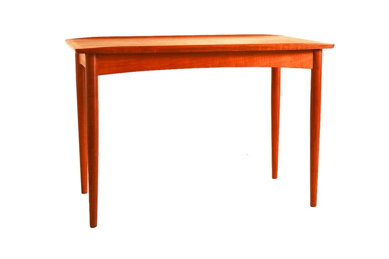 Spectacular 1960s Danish modern teak side table by Mobelintarsia from Denmark. Features a rectangle shaped top in beautifully grained teak with carved lip edges and the sculpted edges are open at the corners. The table stands on four round tapered