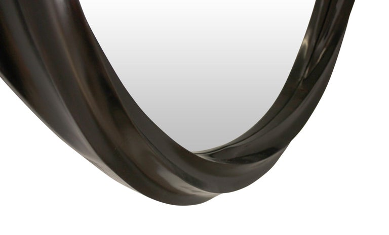 Wave series sculptural spiral wall mirror is presented with a sculptural colixoid frame consisting of 6 interpolated spiral concave surfaces, influenced by works of Moebius. Hard maple frame is stained and toned to a warm dark brown shade with satin