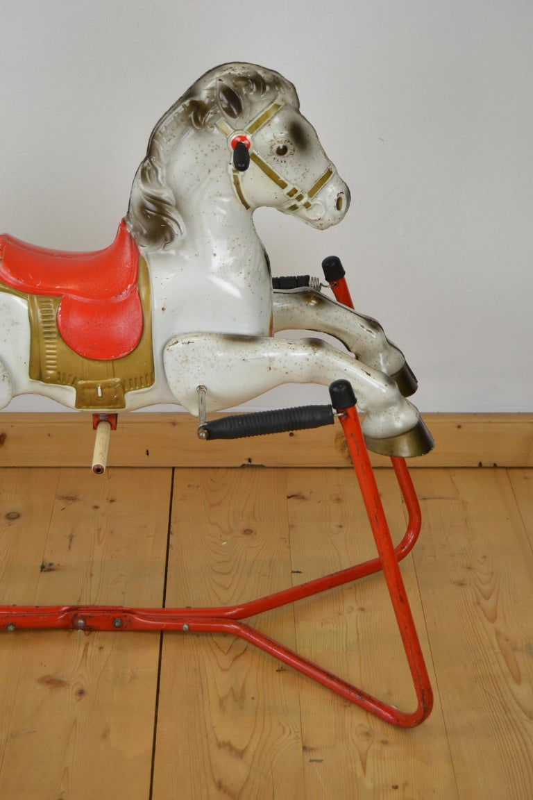 1960s Mobo Prairie King Rocking Horse Toy. This Rocking Horse was made in England by D.Sebel & Co LTD Mobo Toys. This metal horse toy is standing on a frame with springs to rock. With a red saddle and a gold colored saddle cloth or caparison. Made