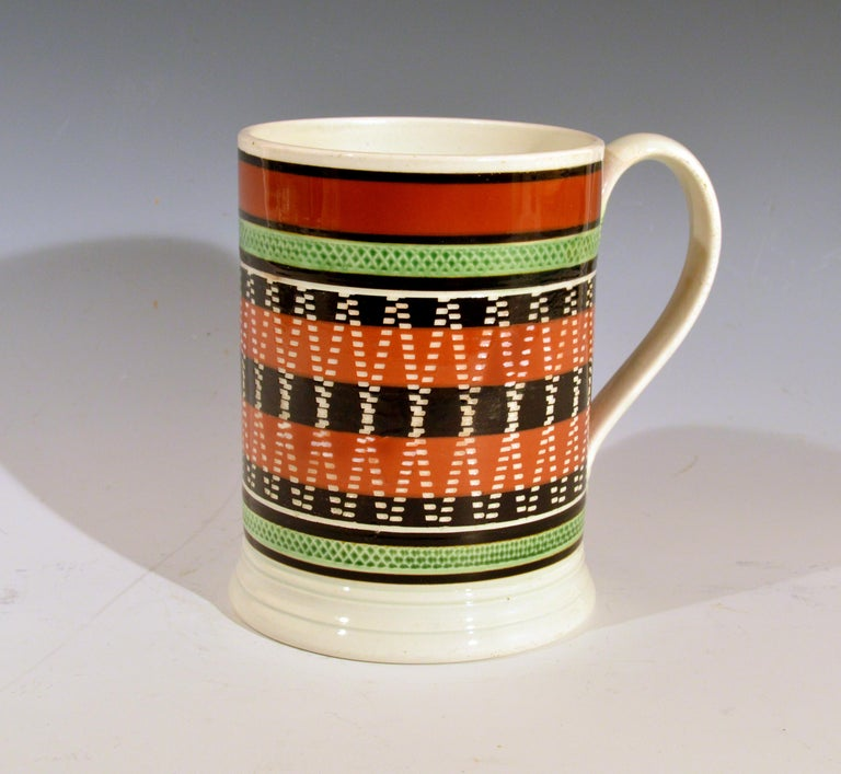 Mocha pottery banded engine-turned Pearlware tankard, circa 1820   The unusually decorated engine turned mocha pottery tankard with a series of five bands around the center in brown and ochre with a rouletted band above and below in green. The