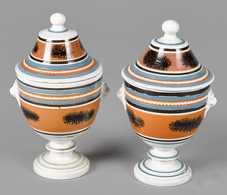 Mocha pottery covered urns with lion-head handles, circa 1825 (Ny9364-crrr)  An unusual pair of mocha urns and covers with a series of slip bands encircling the pots and covers of brown and blue and large central bands in ochre with dendritic