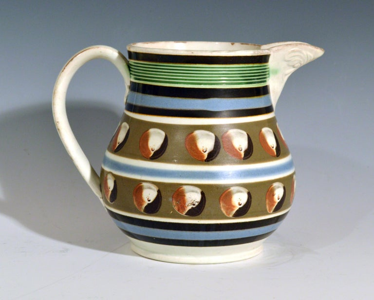 Mocha Pottery double cat's eye-decorated jug, circa 1820  The jug with two bands of a gray-brown ground each with a series of four-color cat's eye-red, brown, white and gray. Three bands of brown and blue above and below and a blue band with