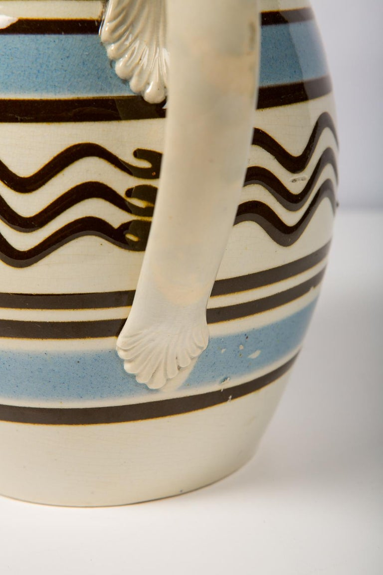 A large mochaware barrel shaped pitcher made of pearl-glazed creamware in the early 19th century. Each mochaware piece is distinctive and this particular pitcher has a unique and unexpected quality: underneath the handle we can see where the artist