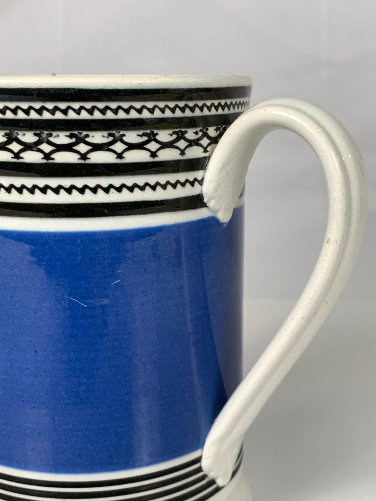 This English mochaware mug is decorated with a wide band of deep royal blue. Above and below the blue are thin black bands, several of which have geometric designs. The body of the mug is pearled creamware which dates the piece to circa 1820.