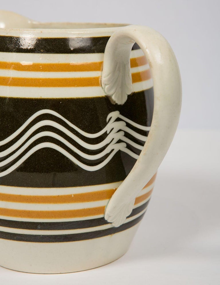 Mocha ware Pitcher. Made in England, circa 1810. Decorated with light and dark brown slip and slip trailing with a single cream color cup with four quills. The strong contrast between the cream-colored wavy lines and the black slip colored ground is