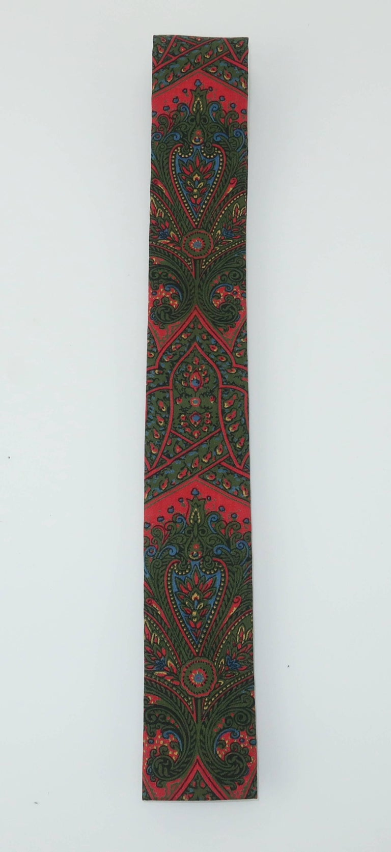 The novelty necktie can be the perfect accessory for a gentleman with both a sense of humor and style.  This 1960's skinny square tie is by Taylor, Ludlow Vermont.  It is fabricated from a cotton blend paisley fabric incorporating a dark orangey