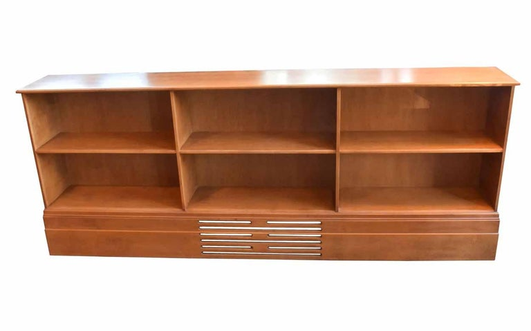 This sleek, solid walnut bookcase is smooth to the touch and in good condition. Decorative fretwork adorns the baseboard, and six spacious compartments will hold your treasured literary collections,  circa 1980. Condition: Good Finish: