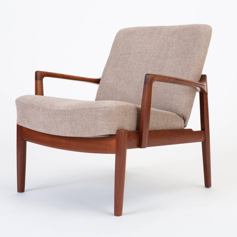 A low, Danish lounge chair by husband and wife design team Tove and Edvard Kindt-Larsen for France & Son. This example from 1958 has a teak frame around fixed cushions, upholstered in a soft taupe textile. The design is distinguished by its bowed