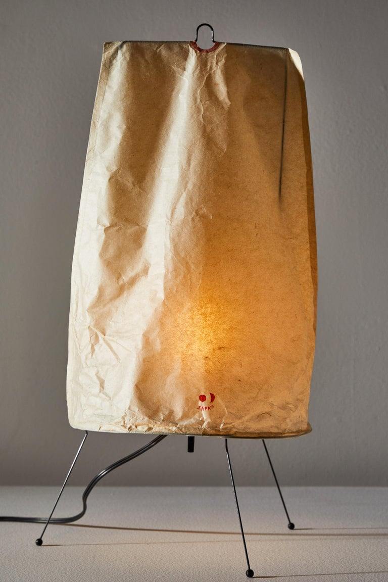 Model 1P table lamp by Isamu Noguchi for Akari. Designed and manufactured in Japan circa 1950s Iron, rice paper. Original early sun and moon stamp. Takes one E26 60w maximum candelabra bulb. Bulbs provided as a one time courtesy.