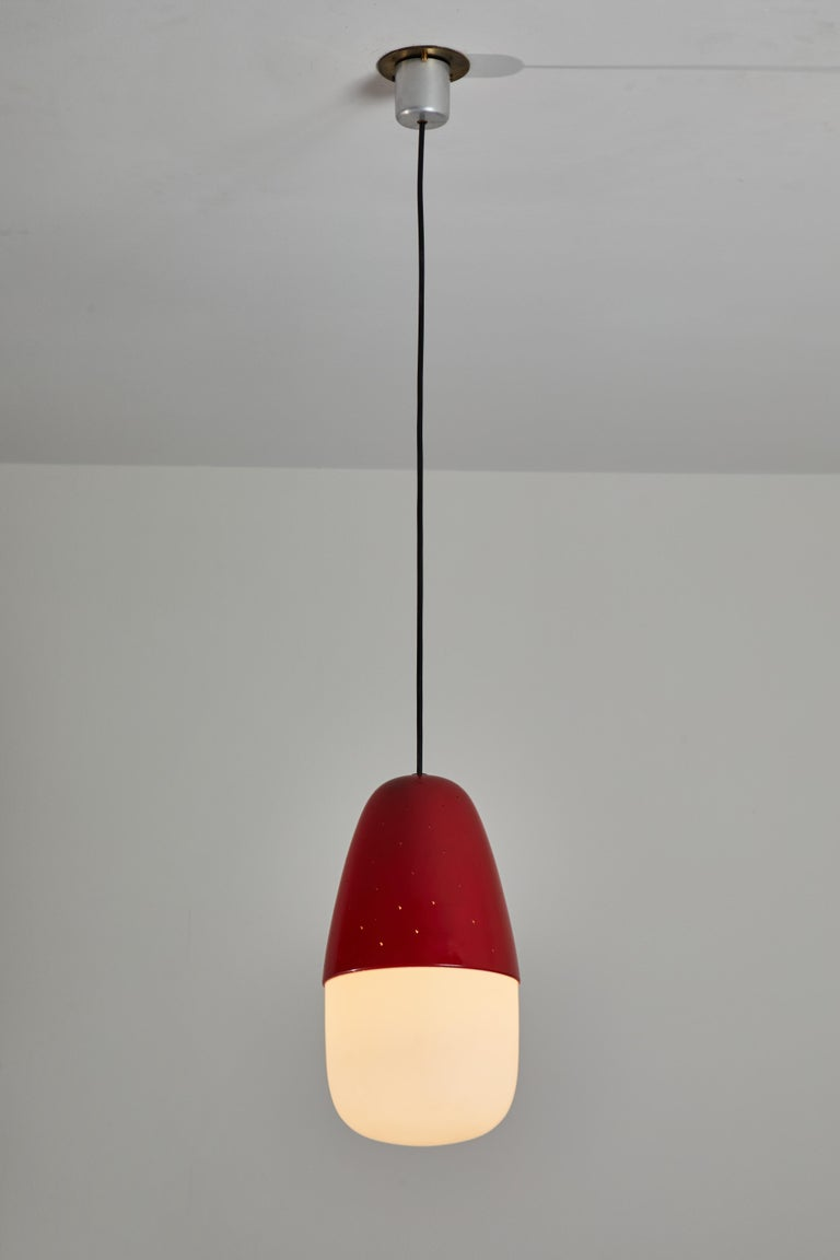 Model 2079 pendant by Gino Sarfatti for Arteluce. Designed and manufactured in Italy, 1955. Opaline glass diffuser, reflector with reversed micro perforated aluminum cup. Lacquered in red. Original canopy with custom brass ceiling plate. Maintains