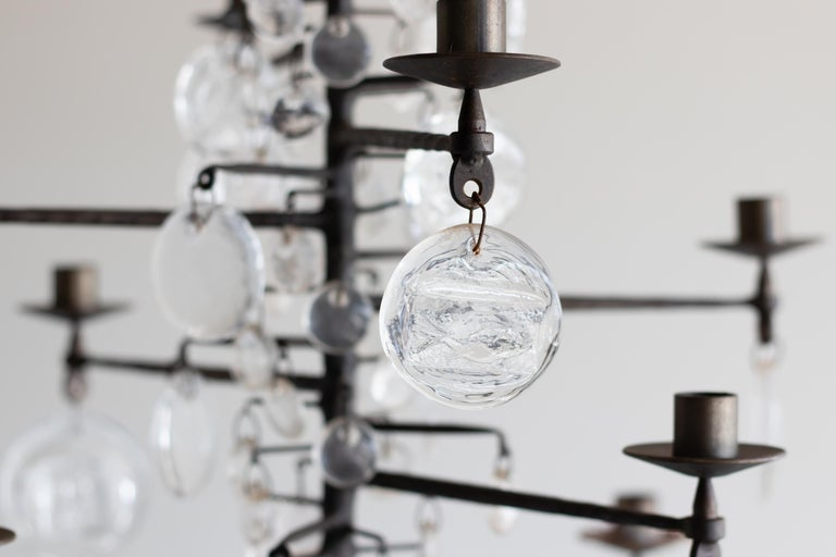 A vintage twelve-arm chandelier designed by Erik Hoglund, Model 341. Glass pendants made by Boda Nova Glassworks; wrought iron frame made by Axel Stromberg Ironworks. Sweden, circa 1957. Features a variety of glass pendants; larger pendants have