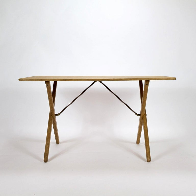 A fully restored midcentury cross-leg oak Model AT308 side table designed by Hans Wegner and made by Andreas Tuck in Denmark, 1950s. Brass and metal struts. New oak veneer on the table top and underside, we have kept the original designer's and