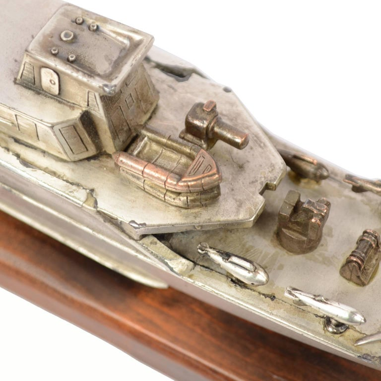 Model of an Italian Navy 5500 ship, made of chromed brass and mounted on a wooden base; made in the 1970s. Measurements of the base cm 35.5 x 5 x total height 7.7 cm. Very good condition.