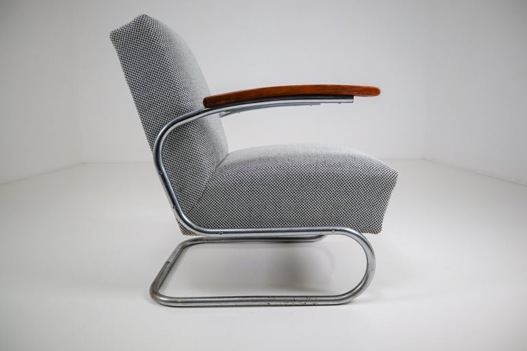 Model S411 armchairs by Thonet circa 1930s midcentury Bauhaus period. These cantilever armchairs are typical for the German and Eastern Europe Bauhaus era. These armchairs has a tubular steel frame and is Re-upholstered with a grey fabric. The