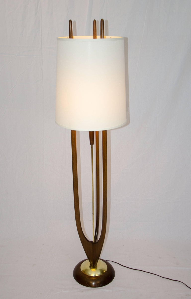 Very nice design floor lamp by the popular Modeline Lamp Co. The wood base is accented by a smaller brass circle. The center brass post holds the electrical cord; the original interior shade is positioned in the center of three walnut posts. The on