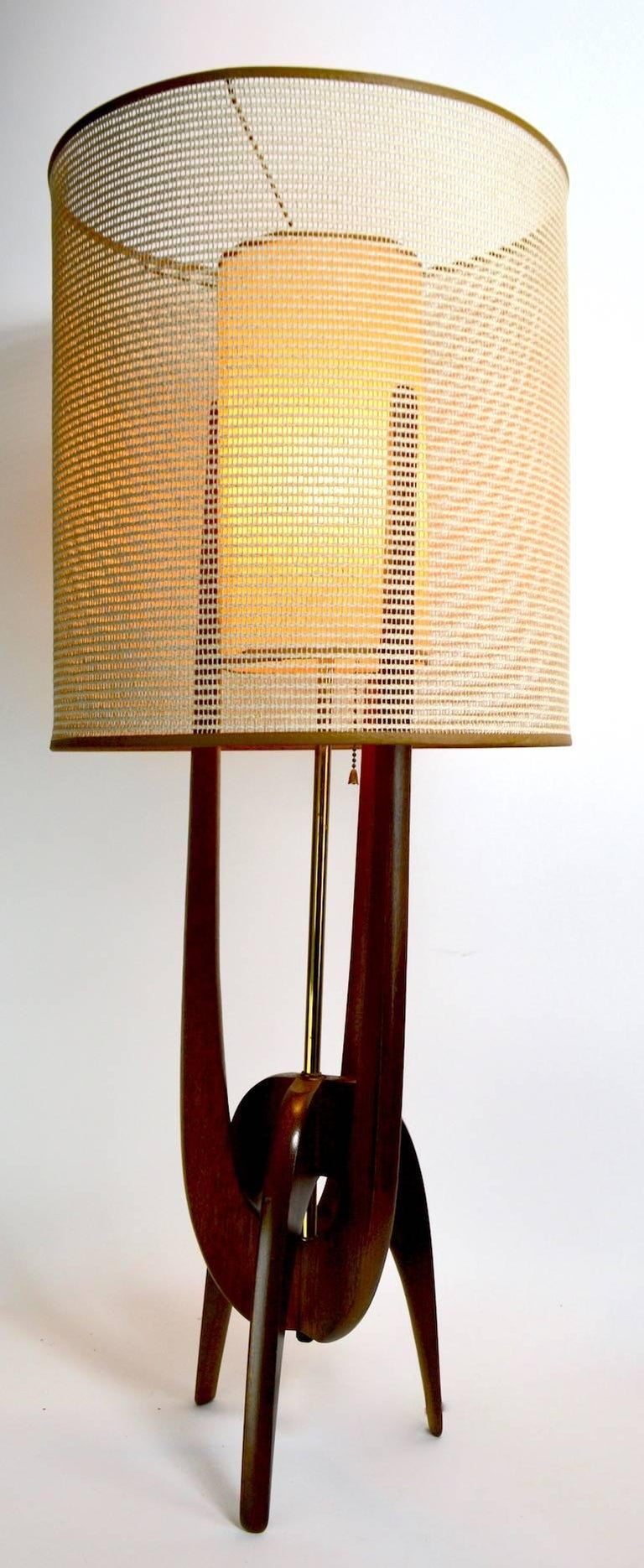 Classic midcentury lamp by Pearsall. This example is in very good, original, clean and working condition. It features the original weave outer shade and textured inner cylinder shade, on sculpted wood bass. Measure: Shade alone 14.75 diameter x