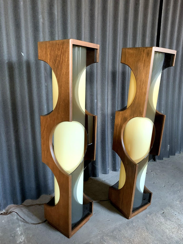 Incredible pair of large scale lamps by Modeline of California. Walnut wood. No breaks or chips anywhere. Smoked Lucite. Center is an opaque acrylic cylinder which houses two bulbs each. Cylinders have yellowing as shown in the photos. Not