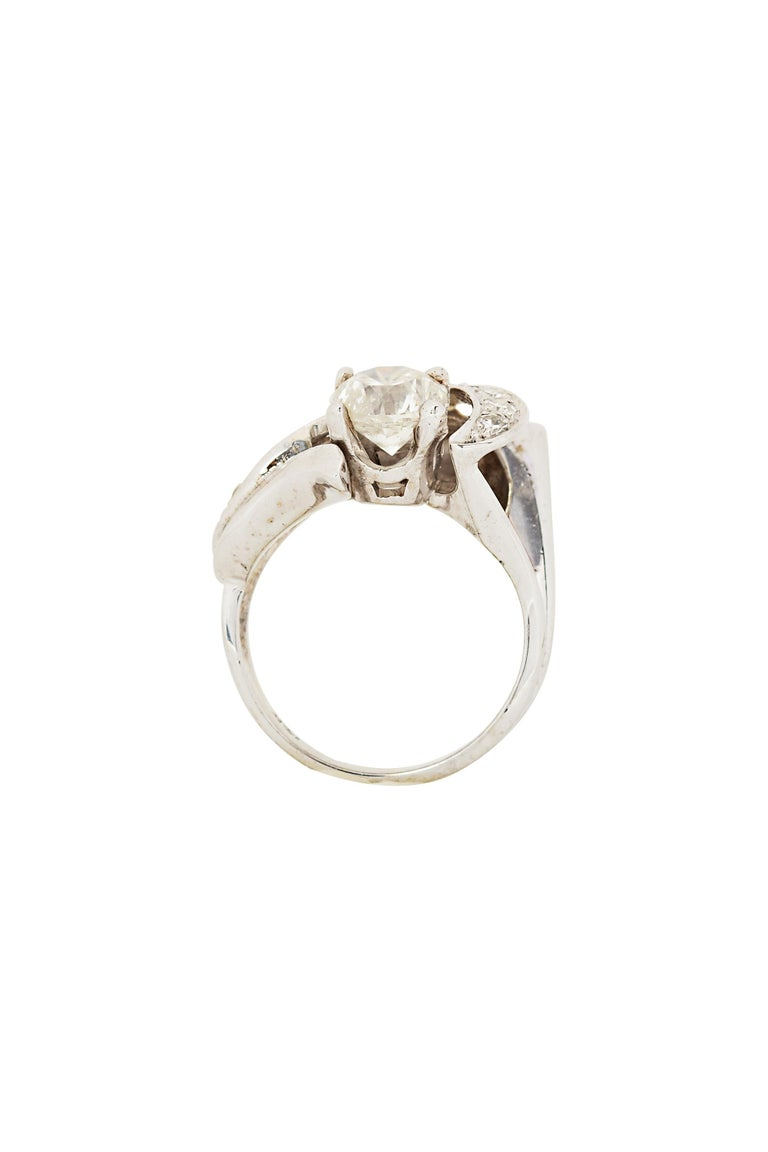 A graceful diamond ring centering a round brilliant diamond of J color, SI2 clarity weighing approximately 1.50 carats, accented by a swirl of sparkling round diamonds in a sculptural 14 karat white gold mounting. The diamond swirl is composed of