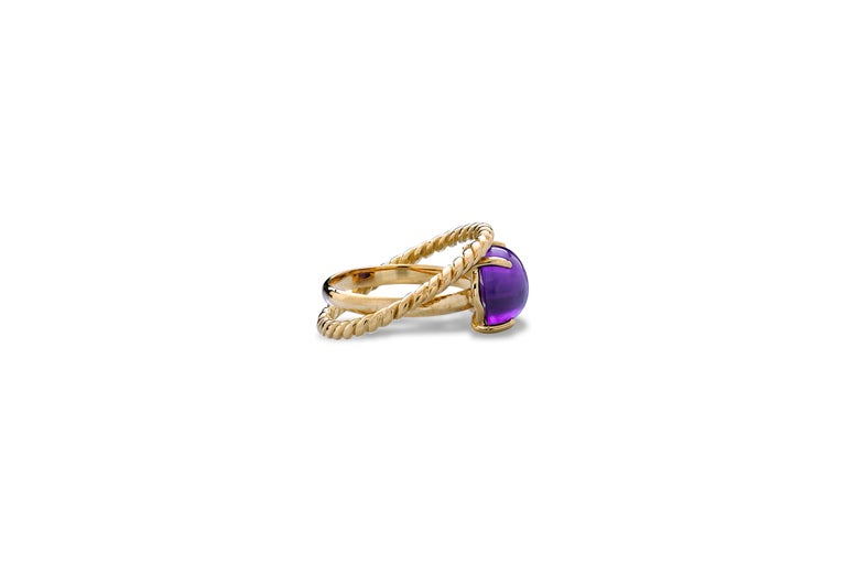 Modern 18 Karat Yellow Gold Twist Love Amethyst Handcrafted Design Ring. This ring is handcrafted with two strips intertwined together in solid 18 karats yellow gold.  A modern style design ring with an oval cabochon amethyst .  Inspired by the