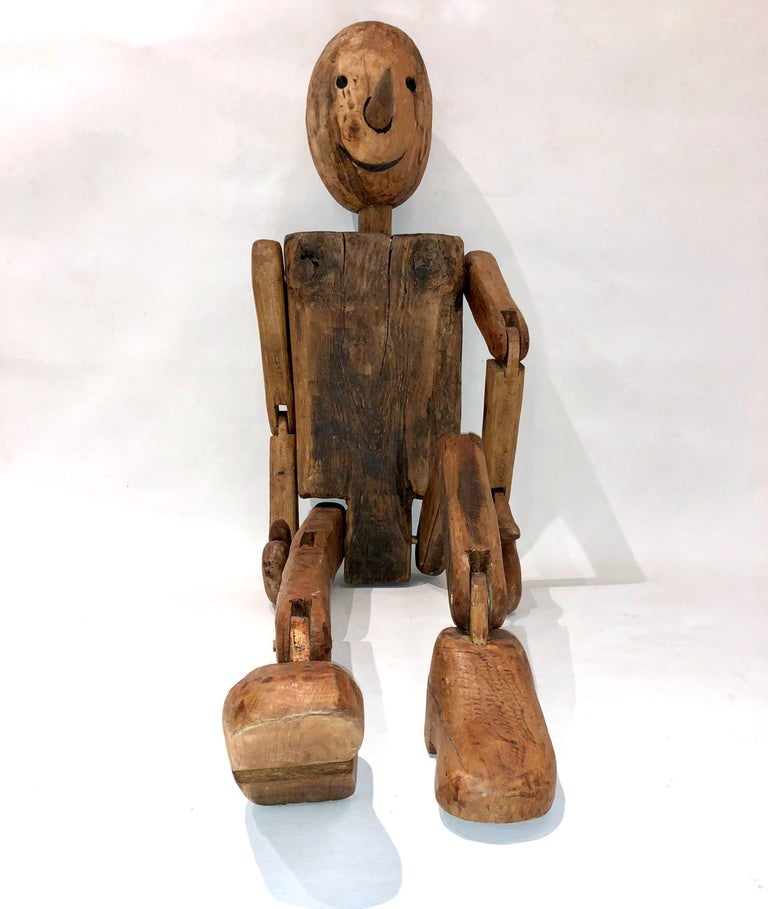 A mid-20th century life-sized Pinocchio modern Folk Art sculpture found in Tuscany, Italy, hand carved in Italian walnut and oak, high quality of the organic execution with articulated arms, hands, legs and feet, rare fun and expressive Work of Art.