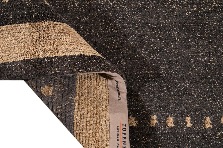 Beautiful modern Tibetan hand knotted wool rug with the gray, brown, and beige field in a gorgeous all-over geometric abstract design.  This rug measures: 9' x 12'.
