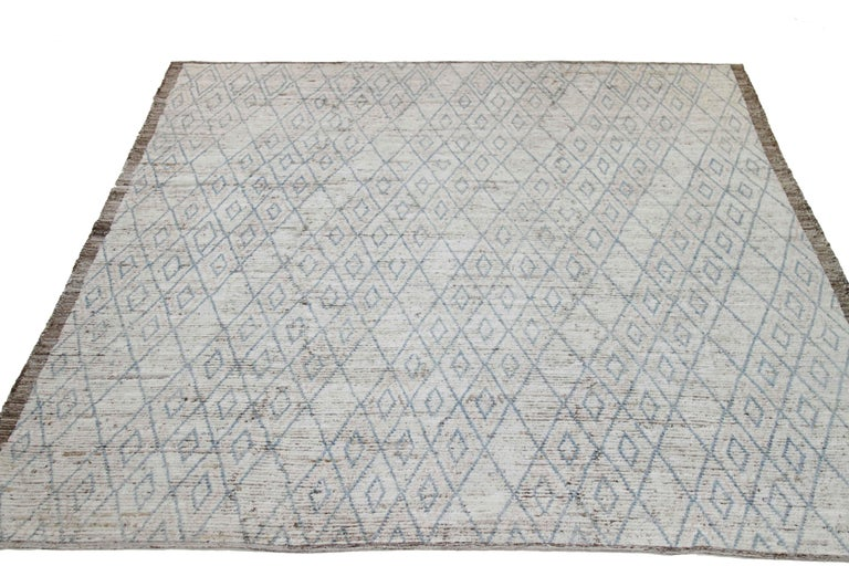 Modern Afghan rug handwoven from the finest sheep's wool and colored with all-natural vegetable dyes that are safe for humans and pets. It's a traditional Afghan weaving featuring a Moroccan inspired design highlighted by blue tribal diamond details
