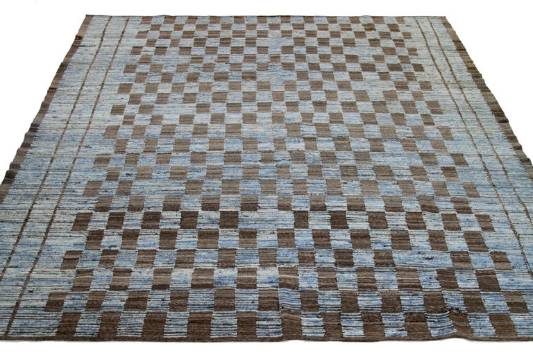 Modern Afghan rug handwoven from the finest sheep's wool. It's colored with all-natural vegetable dyes that are safe for humans and pets. This piece is a traditional Afghan weaving featuring a Moroccan inspired design. It's highlighted by brown tile