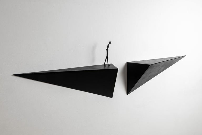 Console composed by two pyramid-shaped elements in patinated waxed metal for Dilmos Milano.  A figure with a pensive look crosses one element of the shelf, directed towards an unknown destination. The measurements of the console are not fixed, as