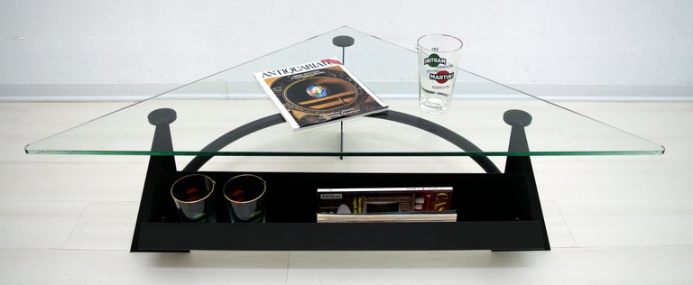 Modern Italian coffee table, base in blackened metal with magazine rack and triangular-shaped glass top, 1990.
