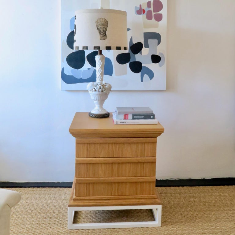The Martin & Brockett Frieze night stand is a three-drawer column with architectural cap and base details in scrubbed oak. It rests upon a white powder-coated pedestal. Three drawer configuration, with integrated finger pulls.  Part of our Frieze