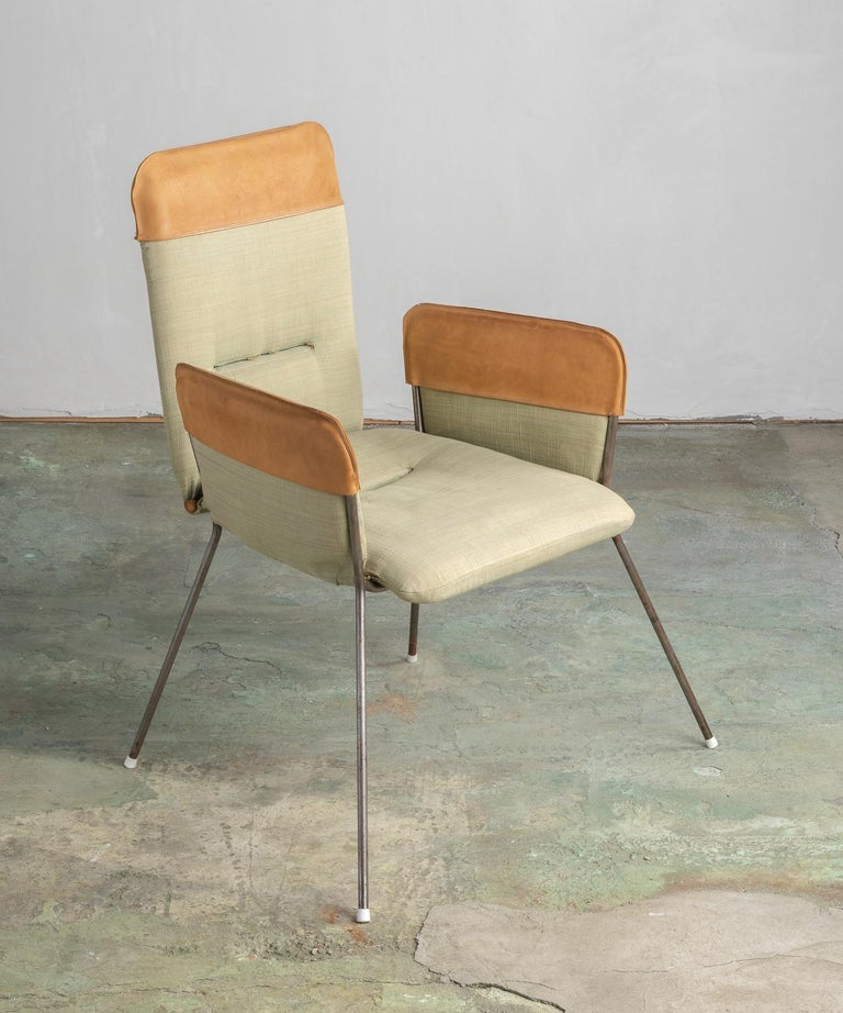 Modern armchair, America, 20th century.  Simple form includes original upholstery and leather accents.