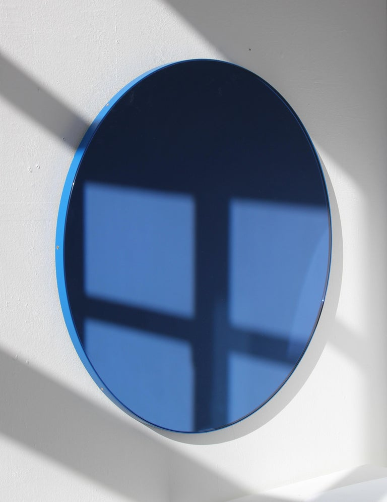 Delightful handcrafted blue tinted round mirror with a funky blue frame. Designed and hand-crafted in London, UK. The detailing and finish, including visible screws, emphasize the craft and quality feel of the mirror, a true signature of our brand.