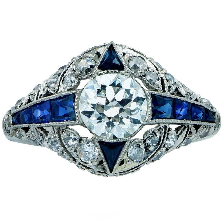 Platinum ring featuring a .93ct European cut diamond I color and VS2 clarity surrounded by .51cts of European cut diamonds and 10 royal blue sapphires weighing .40cts total.  Size - 6  Our pieces are all accompanied by an appraisal performed by one