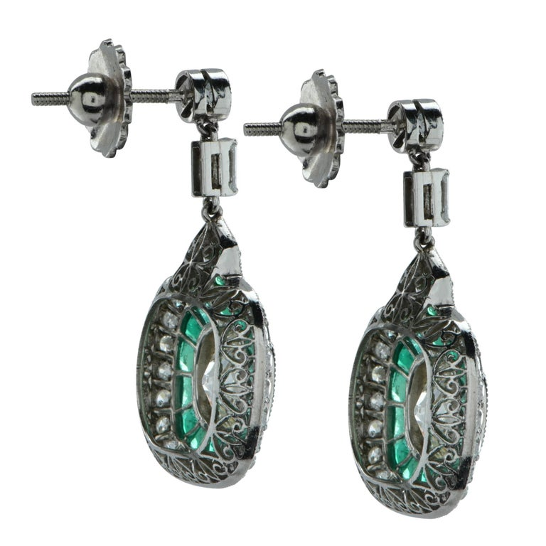 Stunning modern Art Deco style  articulating dangle earrings featuring 2 antique old mine cut diamonds weighing approximately 3.2 carats total, H color, SI clarity, set in platinum and framed with milgrain. The diamonds rest on a bed of 30 vivid