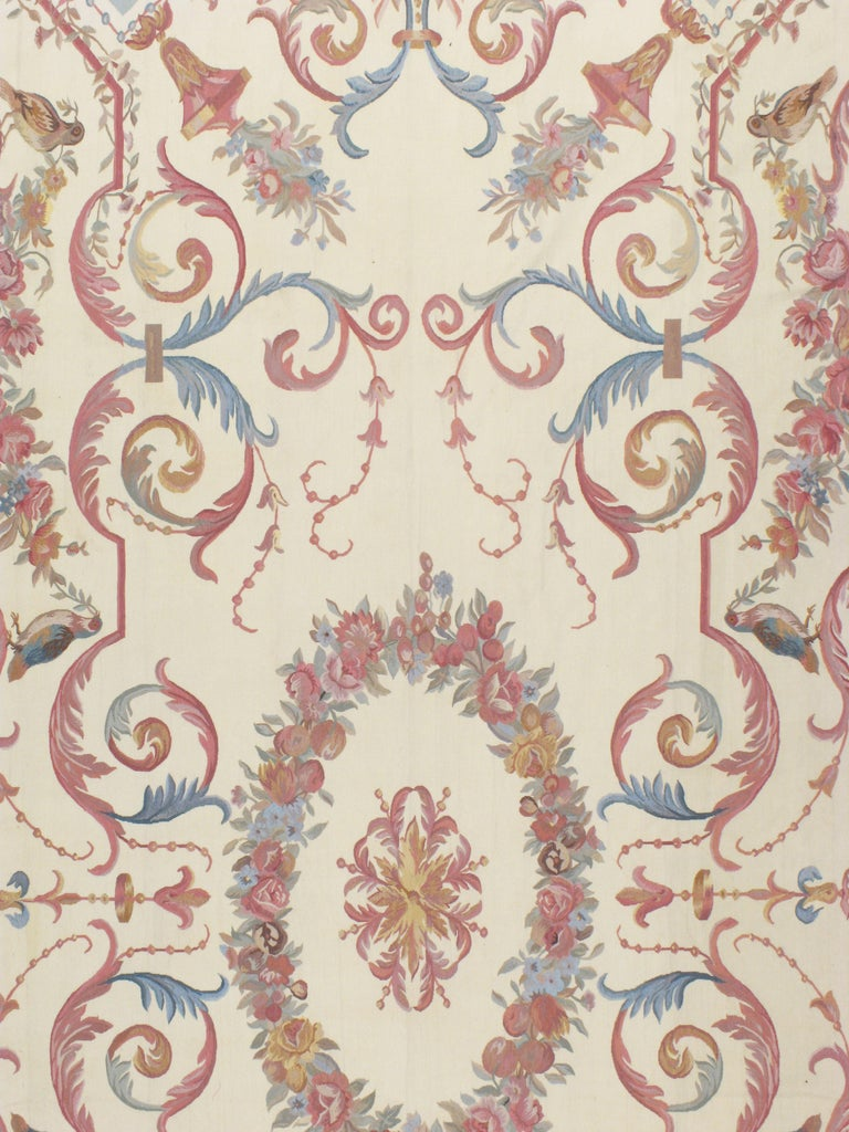 A handmade contemporary reproduction of the timeless French Aubusson carpet in the style of Louis XV. The floral pattern consists of colors including rose, blue, and grey, over an Ivory background. Grandeur in size and regal in design.